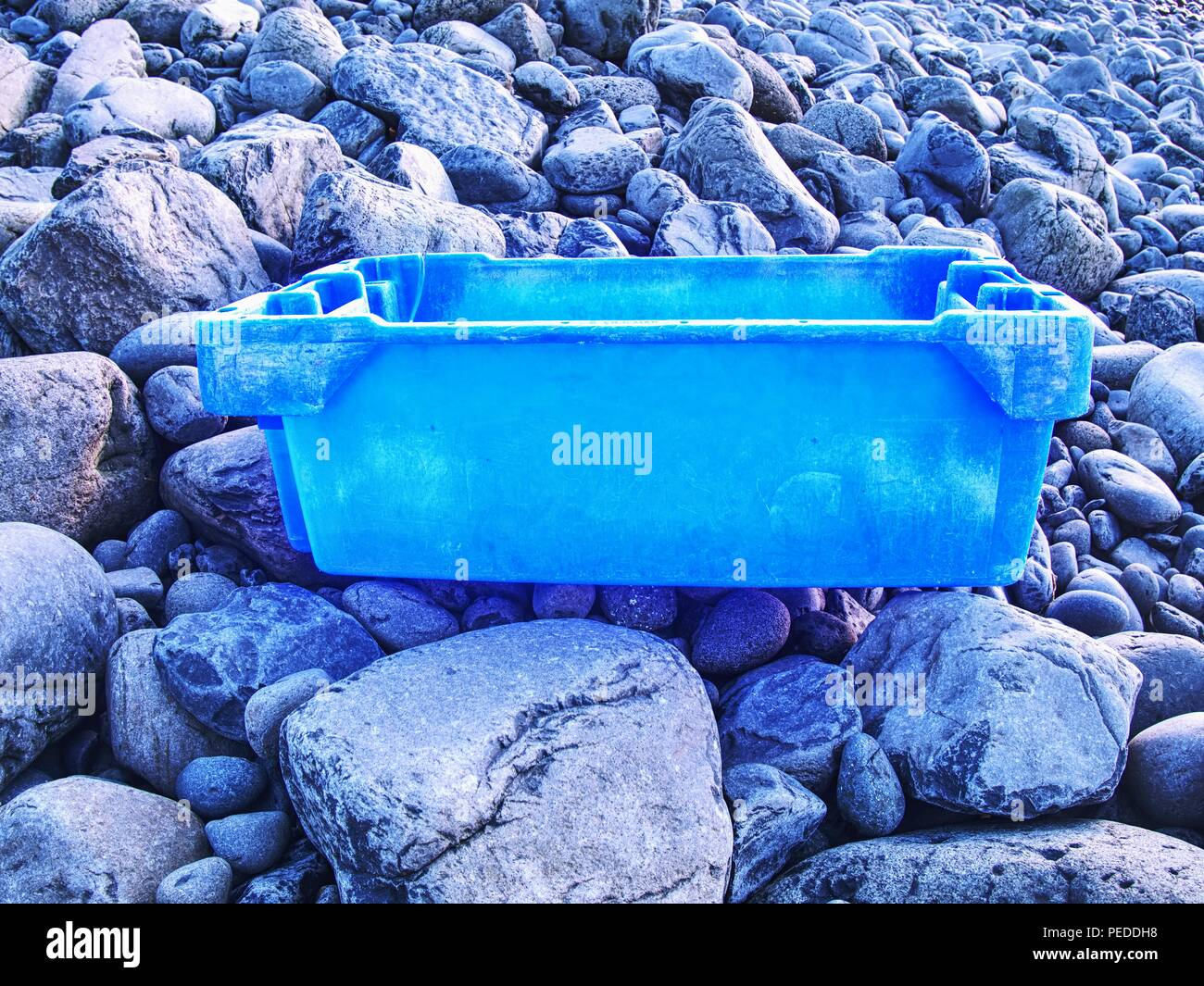 Dangerous garbage ejected from the sea on remote beaches. Environmental contamination with toxic mess. - Stock Image