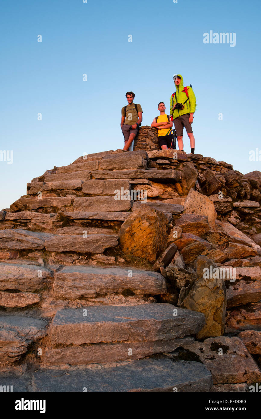 Snowdon summit with 3 walkers stood admiring the sunset. - Stock Image