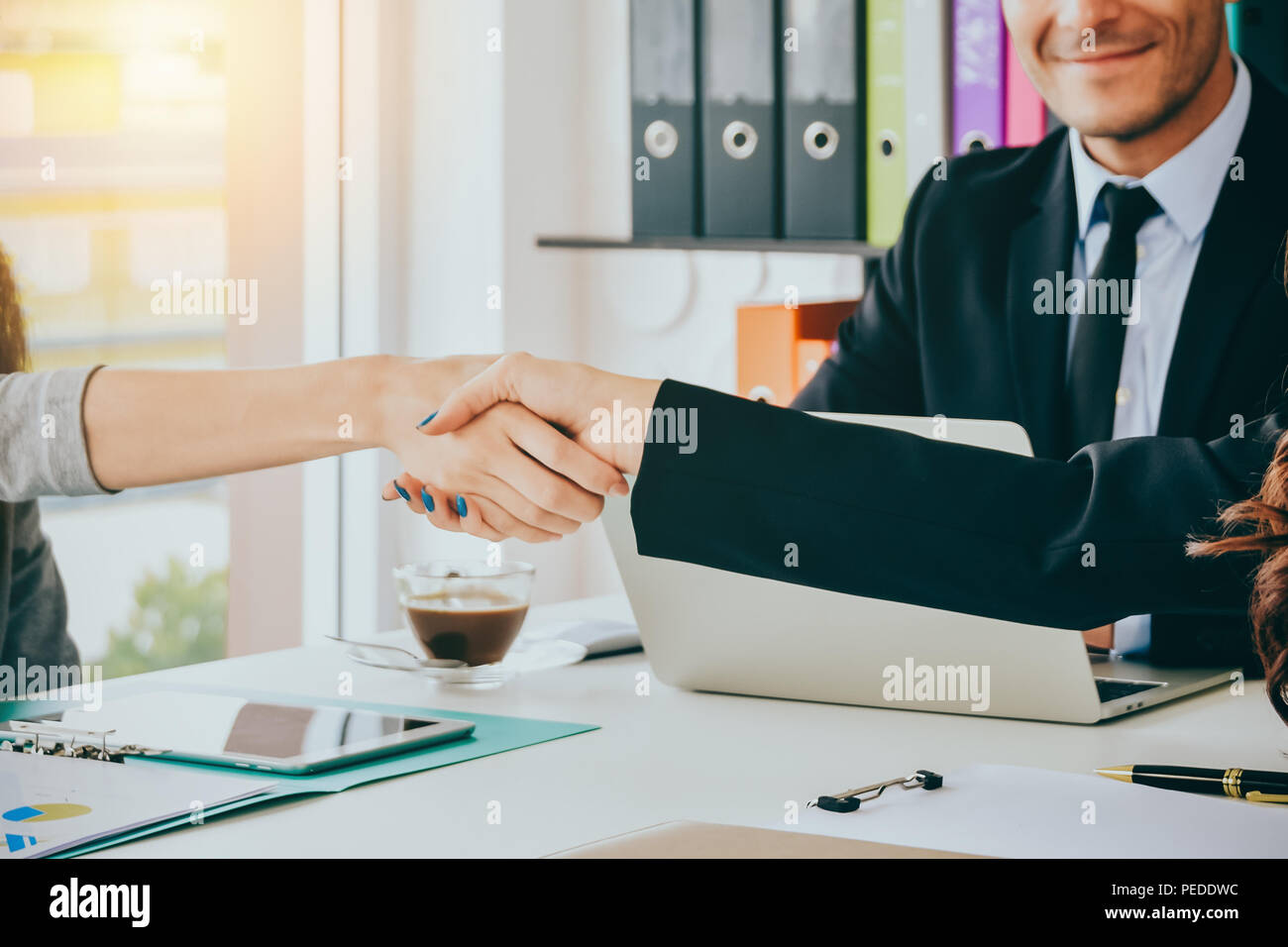Close up Business women shaking hands during a meeting in the office with blurred business happiness people :business team partnership concept - Stock Image