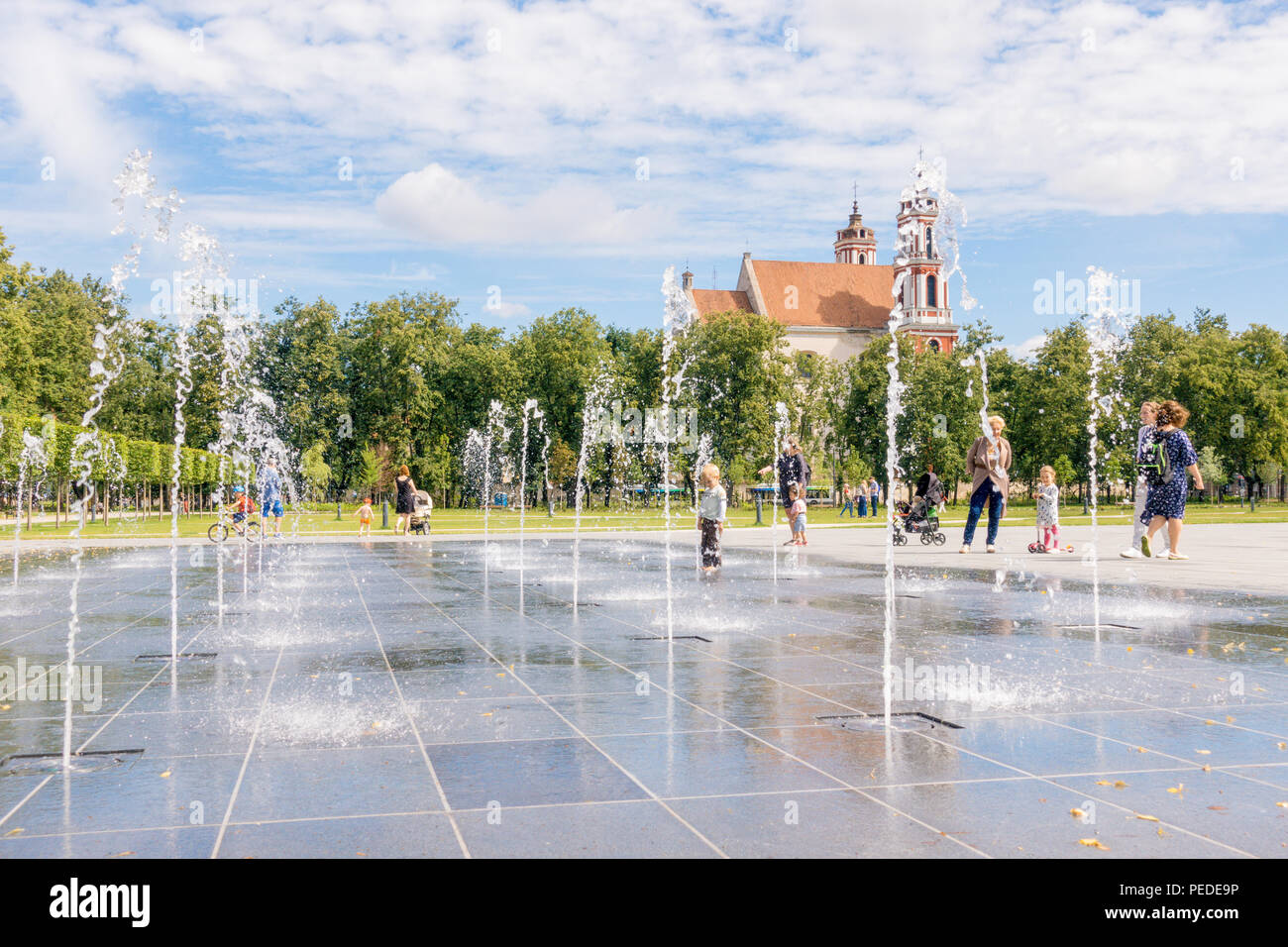People have fun playing in city water fountain on hot summer day in Lukiskes square - Stock Image