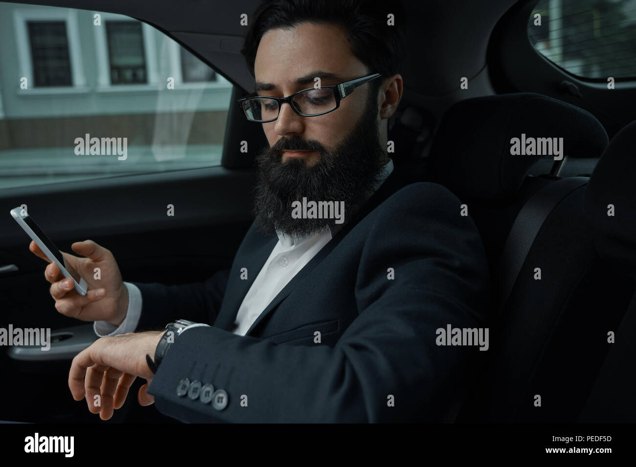 A businessman while traveling by car in the back seat using a sm - Stock Image