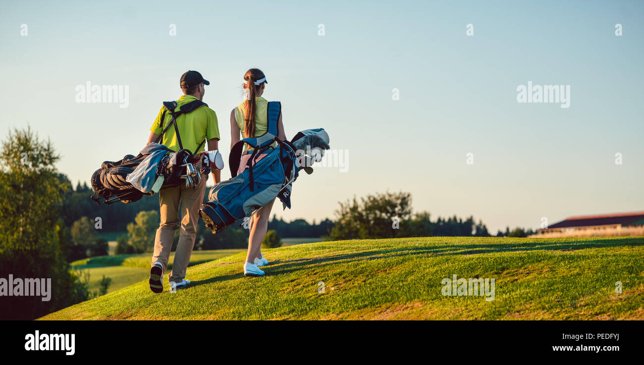 Happy couple wearing golf outfits while carrying stand bags - Stock Image