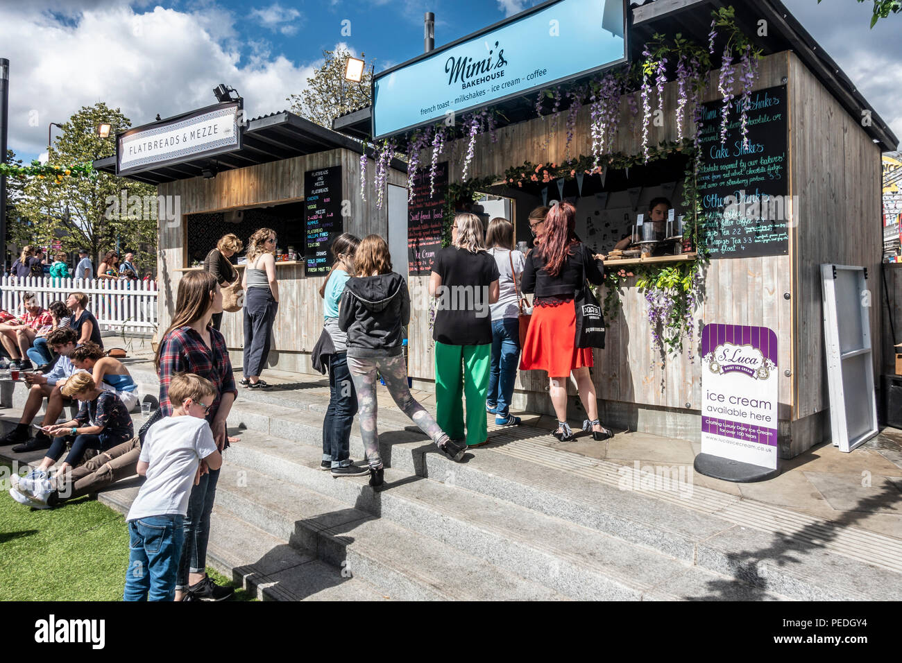 Visitors to Edinburgh Festival Fringe enjoying August sunshine and queuing at pop-up food stalls, Mimi's Bakehouse and Flatbreads & Mezze in Bristo Sq - Stock Image