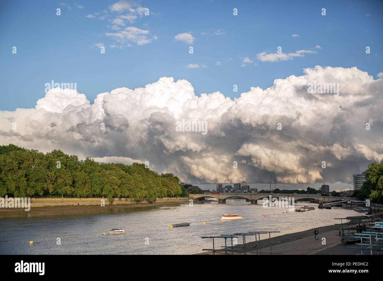 Huge cumulonimbus cloud (big fluffy storm cloud) over the River Thames in South West London (near Putney and Fulham) - Stock Image
