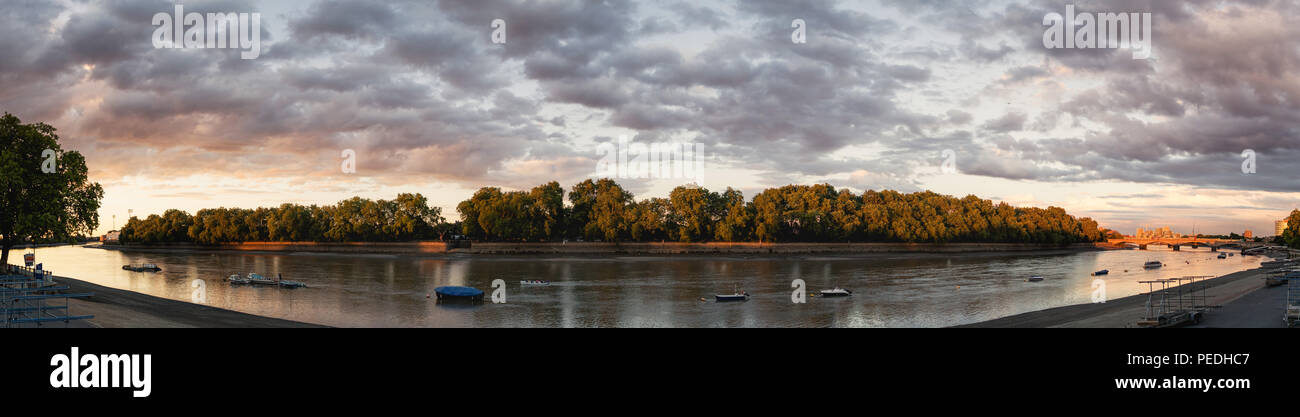 Panoramic view of the river Thames in Putney looking towards Fulham (Bishop's Park) with rowers rowing a boat in the distance. Sunset. Big sky. Clouds - Stock Image