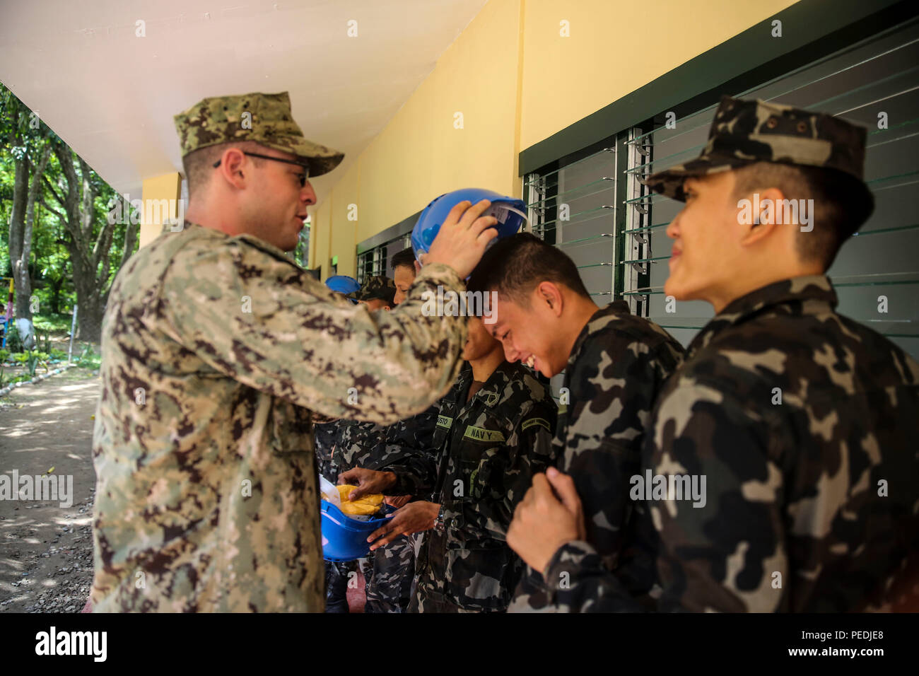 150811-M-GO800-262 FERNANDO CITY, Philippines (Aug. 11, 2015) – Seabees with Mobile Construction Battalion Five present construction helmets to members of the Philippine navy during a ribbon cutting ceremony at Boy-Utan Elementary School official opening it up for use Aug. 11. Task Force Forager will be in the Philippines until Aug. 15 providing medical and engineering assistance. Task Force Forager, embarked aboard the Military Sealift Command joint high speed vessel USNS Millinocket (JHSV 3) is serving as the secondary platform for Pacific Partnership, led by an expeditionary command element - Stock Image