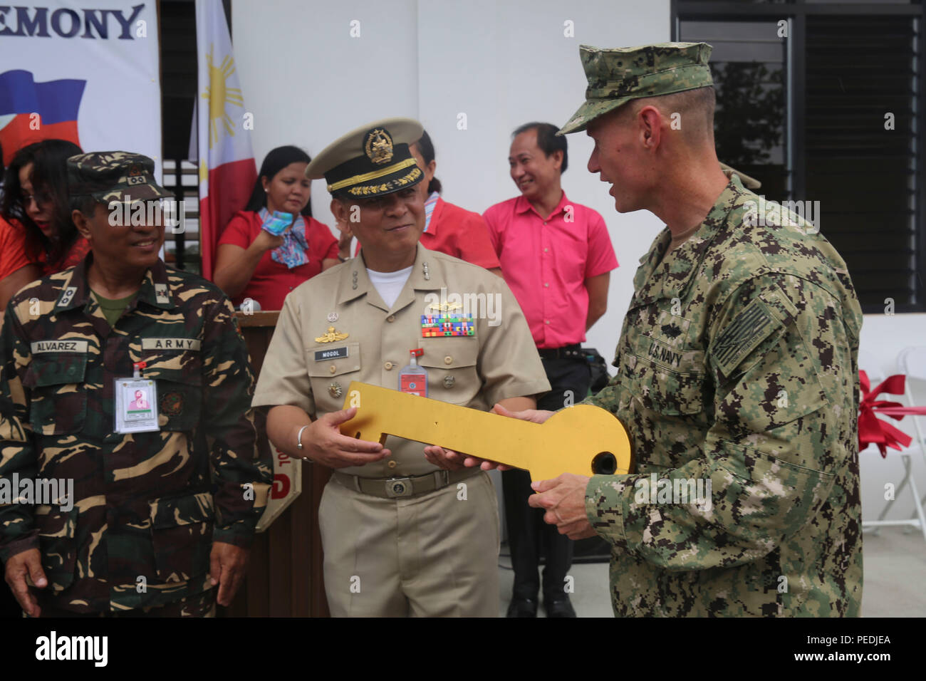 150810-M-GO800-312 SAN FERNANDO CITY, Philippines (Aug. 10, 2015) – Commodore, Task Force Forager Capt. James Meyer passes the key to Eulogio Clarence M. De Guzman Elementary School to Philippine navy Capt. Albert Mogol during a ribbon cutting ceremony Aug. 10. Task Force Forager will be in the Philippines until Aug. 15 providing medical and engineering assistance. Task Force Forager, embarked aboard the Military Sealift Command joint high speed vessel USNS Millinocket (JHSV 3) is serving as the secondary platform for Pacific Partnership, led by an expeditionary command element from the Navy's - Stock Image