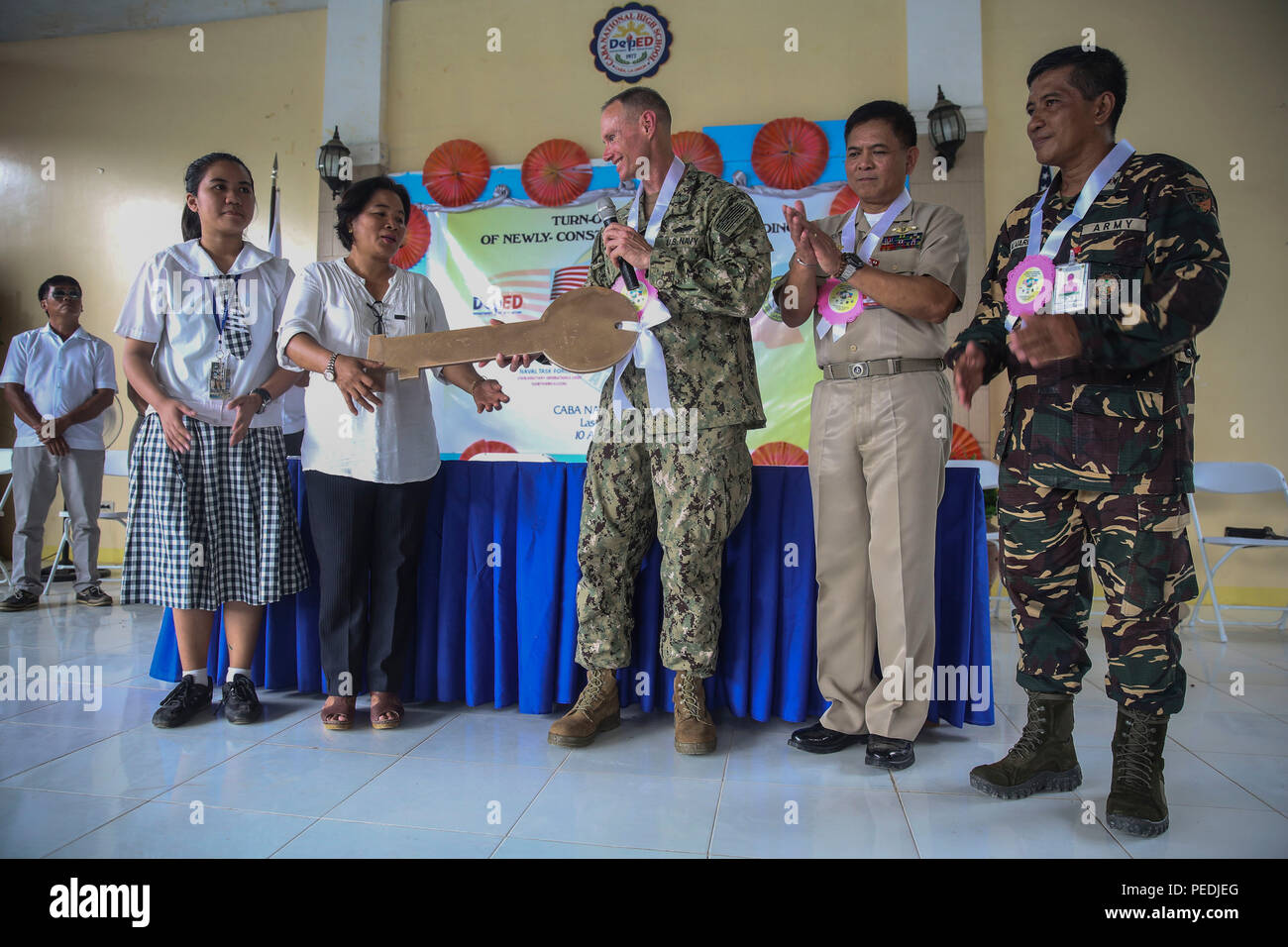 150810-M-GO800-558 SAN FERNANDO CITY, Philippines (Aug. 10, 2015) – Commodore, Task Force Forager Capt. James Meyer passes the key to Caba National High School to Josefina Samy during a ribbon cutting ceremony Aug. 10. Task Force Forager will be in the Philippines until Aug. 15 providing medical and engineering assistance. Task Force Forager, embarked aboard the Military Sealift Command joint high speed vessel USNS Millinocket (JHSV 3) is serving as the secondary platform for Pacific Partnership, led by an expeditionary command element from the Navy's 30th Naval Construction Regiment (30 NCR)  - Stock Image