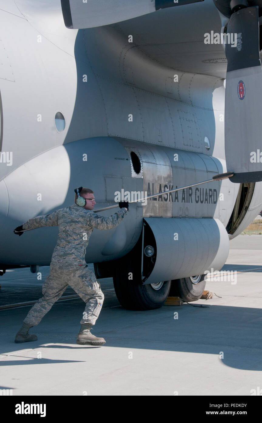 Staff Sgt. Dayton Osborn, a 176th Aircraft Maintenance crew chief, rotates the blades of a C-130 Hercules aircraft on Joint Base Elmendorf-Richardson, Alaska, Aug. 11, 2015, for operational integrity. Alaska Air Guardsmen of the 176th Wing train alongside their international counterparts as part of Red Flag-Alaska 15-3. (Alaska Air National Guard photo by Tech. Sgt. N. Alicia Halla/released) - Stock Image