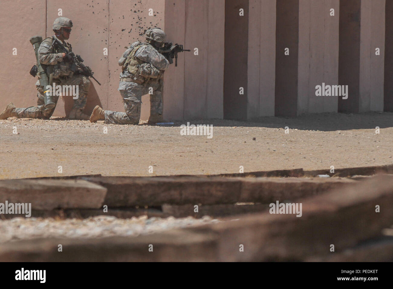 Paratroopers assigned to the 1st Battalion, 325th Airborne Infantry Regiment, 2nd Brigade Combat Team, 82nd Airborne Division, assault an enemy-held urban environment at the National Training Center at Fort Irwin, Calif., Aug. 11, 2015. The 1st Battalion, 325th AIR paratroopers completed several blank and live-fire iterations during the day and at night, enhancing their capability to incorporate myriad echelons of fire and unique weapons as well as sharpening proficiency at battle drills in the austere, arid environment of the Mojave Desert. The 1st Battalion, 325th AIR and other elements of t - Stock Image