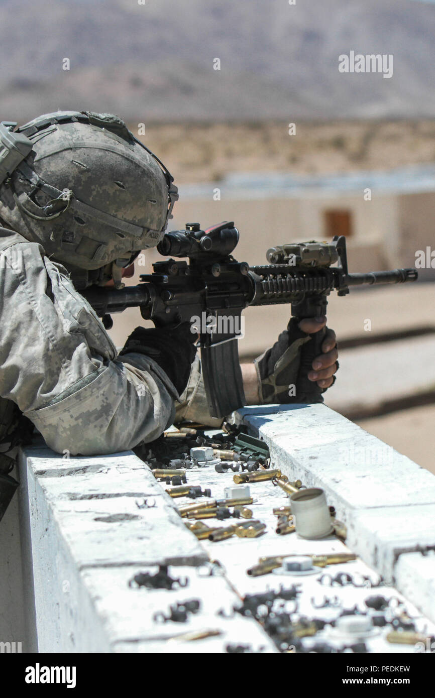 Spc. Scott Hogg, a paratrooper assigned to the 1st Battalion, 325th Airborne Infantry Regiment, 2nd Brigade Combat Team, 82nd Airborne Division, fires at enemy targets during an assault on an enemy-held urban environment at the National Training Center at Fort Irwin, Calif., Aug. 11, 2015. The 1st Battalion, 325th AIR paratroopers completed several blank and live-fire iterations during the day and at night, enhancing their capability to incorporate myriad echelons of fire and unique weapons as well as sharpening proficiency at battle drills in the austere, arid environment of the Mojave Desert - Stock Image