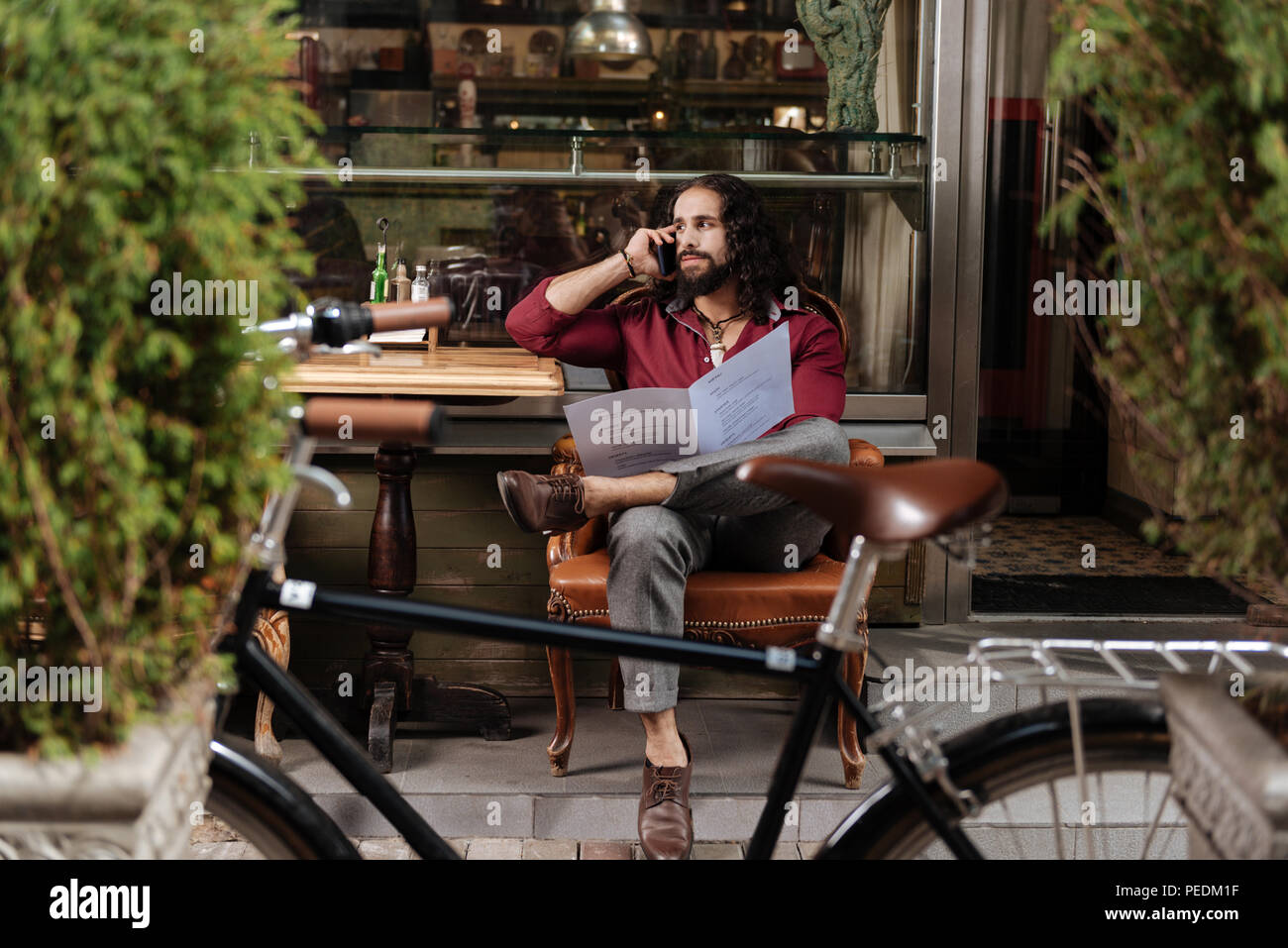 Handsome long haired man making a call - Stock Image