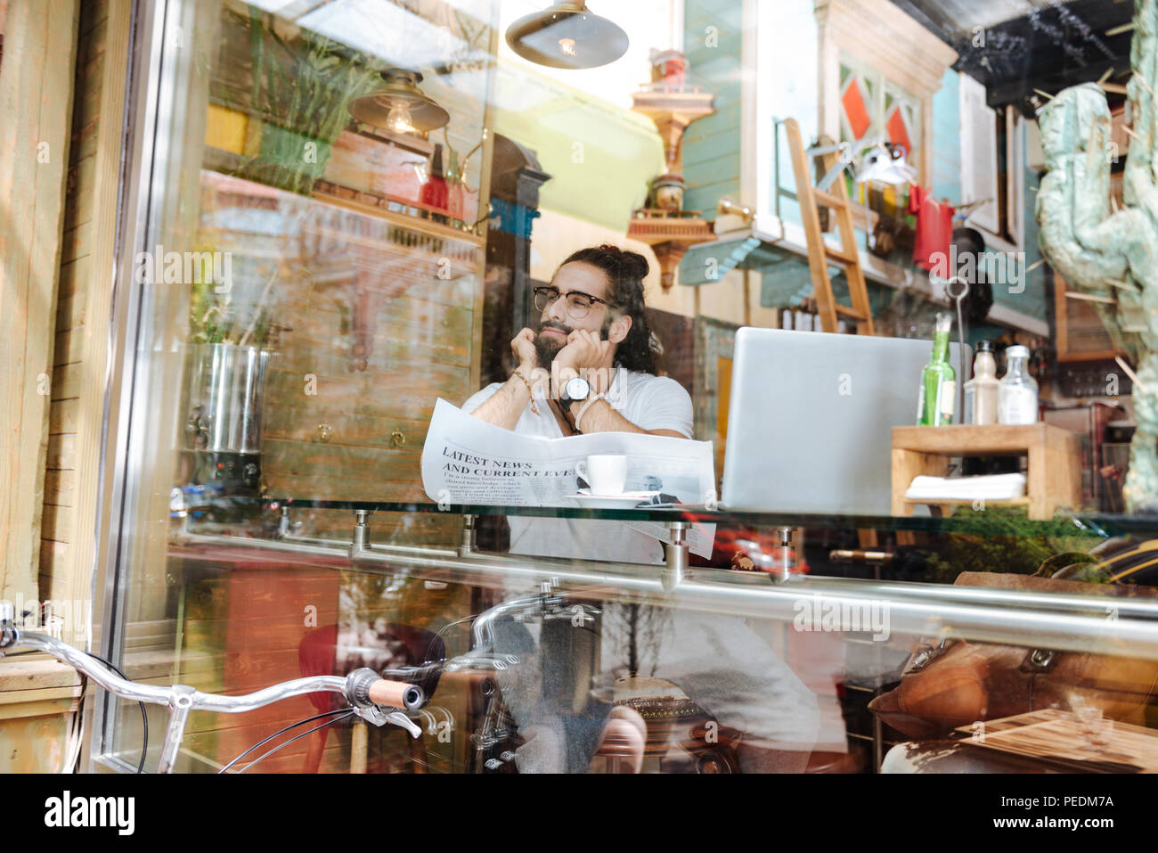 Nice delighted man looking into the window - Stock Image