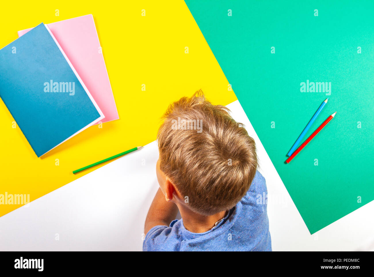Kid with books notebooks pencils over colorful background Stock Photo