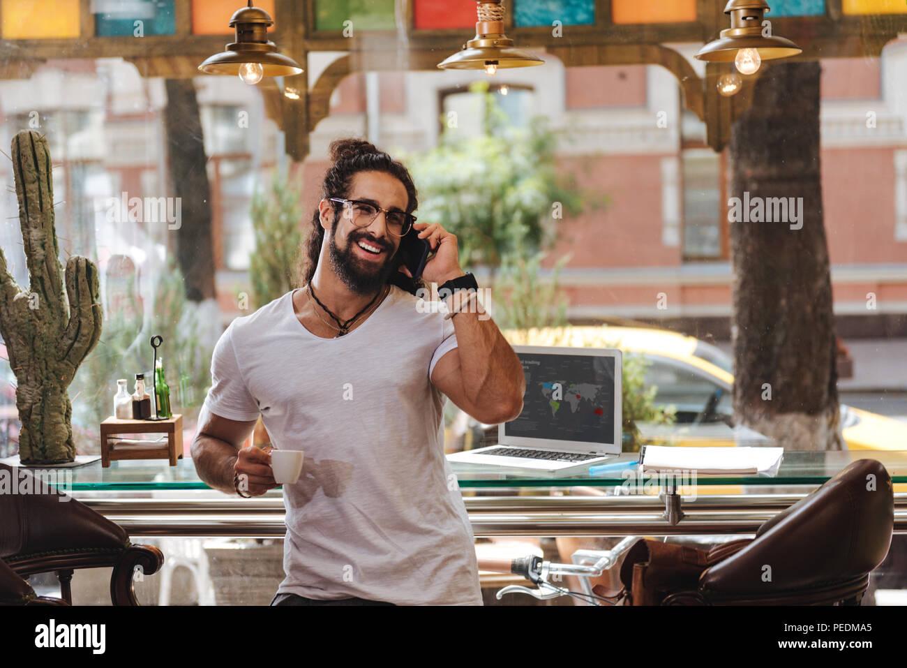 Joyful happy man having espresso - Stock Image