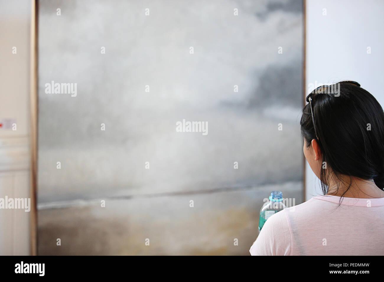 woman admiring art - Stock Image
