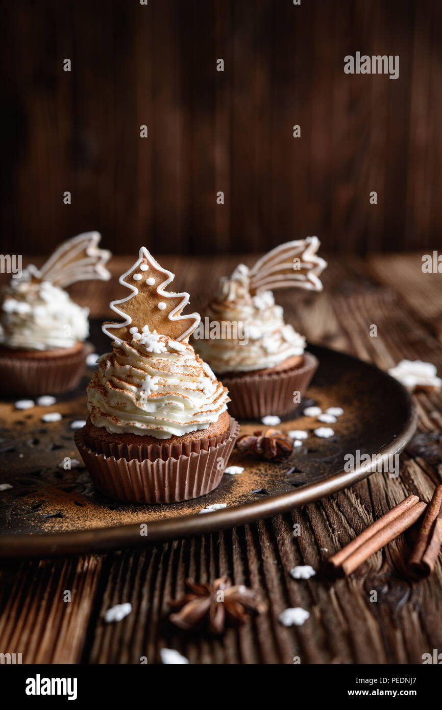 Homemade gingerbread cupcakes decorated with cinnamon and Christmas cookies and snowflake sprinkles - Stock Image