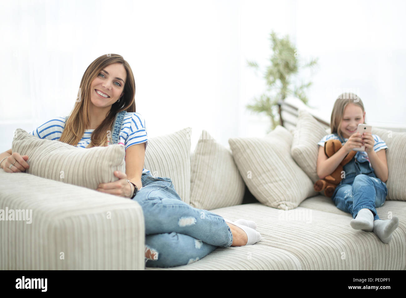 young housewife and her little daughter sitting on the couch - Stock Image