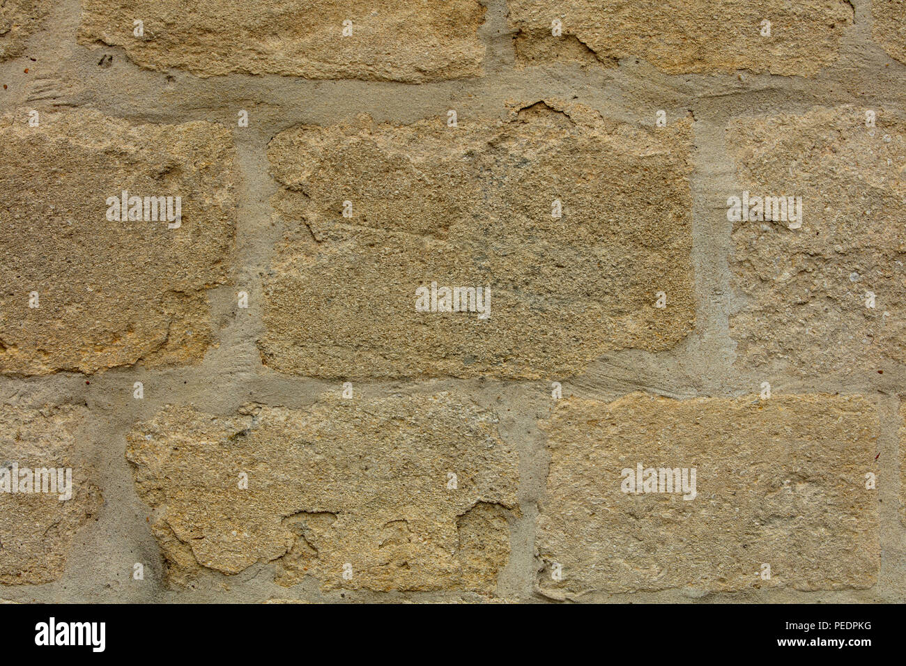 Wall with regular rectangle light coloured natural stones, old town of Norwich, UK - Stock Image