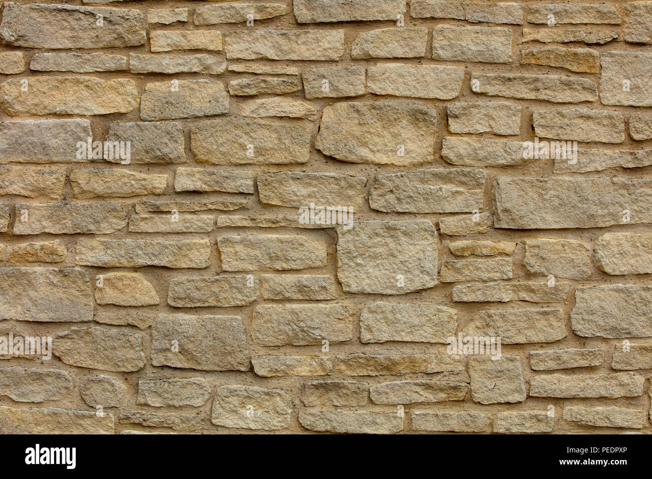 Load bearing wall with horizontal pattern using thin, long thin and square stone, old town of Norwich, UK - Stock Image