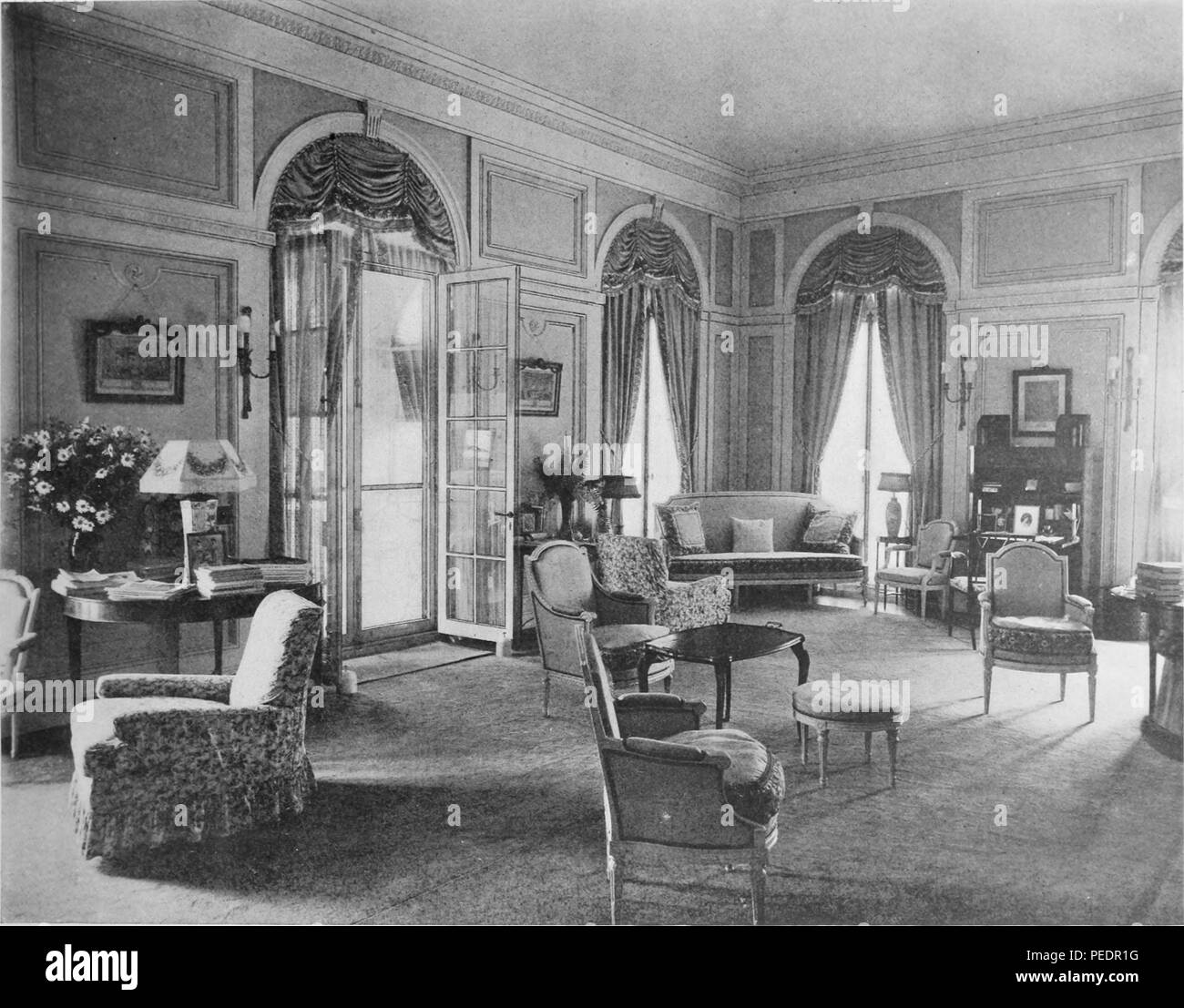Black and white photograph showing an interior view of the library, at the summer home of Oliver Ames Esq, located in Prides Crossing, Massachusetts, designed in the style of a French villa, with paneled walls and arched french doors, 1905. Courtesy Internet Archive. () - Stock Image