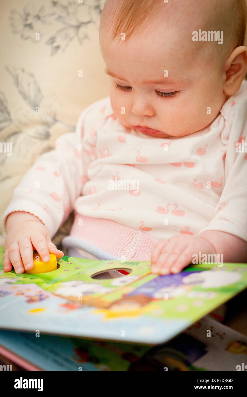 baby girl with book - Stock Image