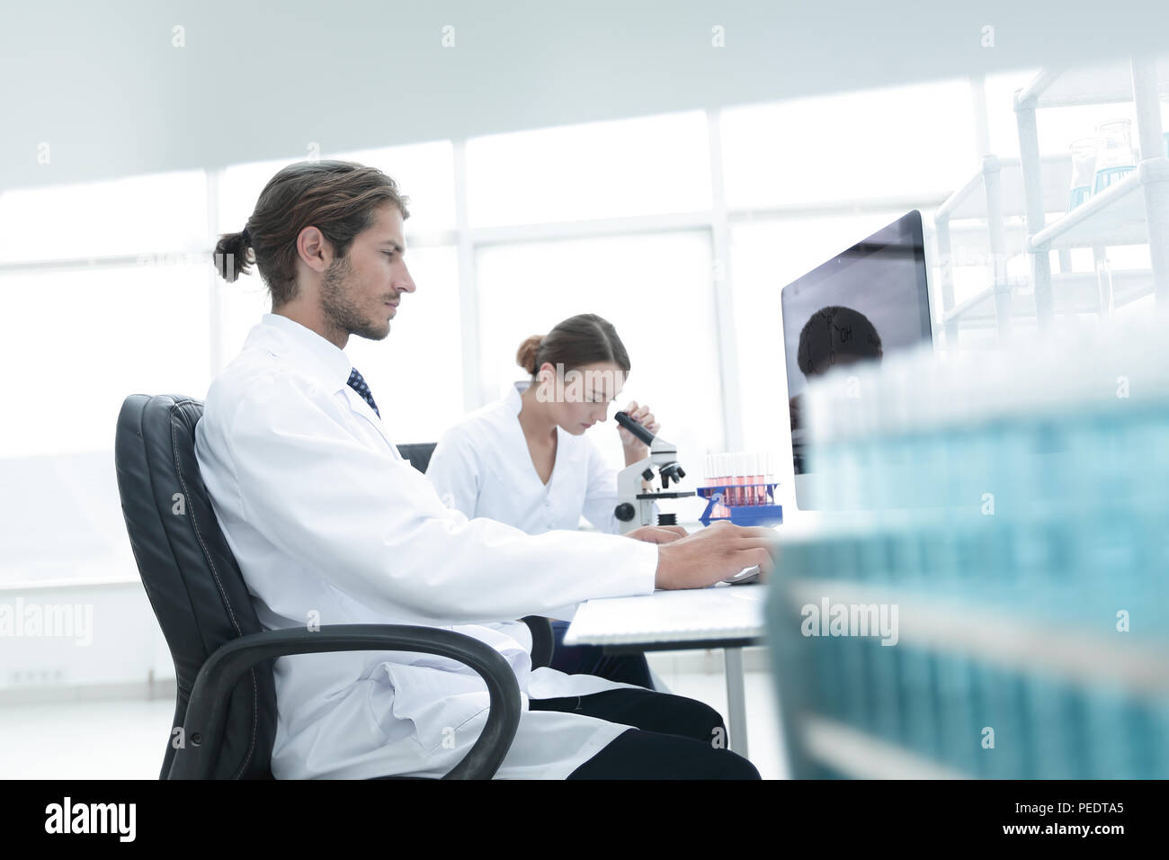Scientist looking at specimen while his assistant helping him - Stock Image