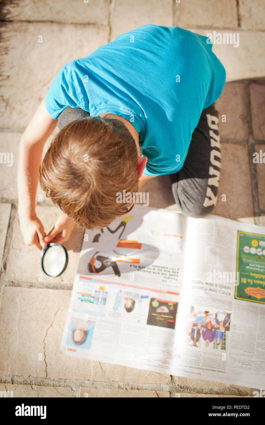 Young boy burning newspaper with a magnifying glass - Stock Image