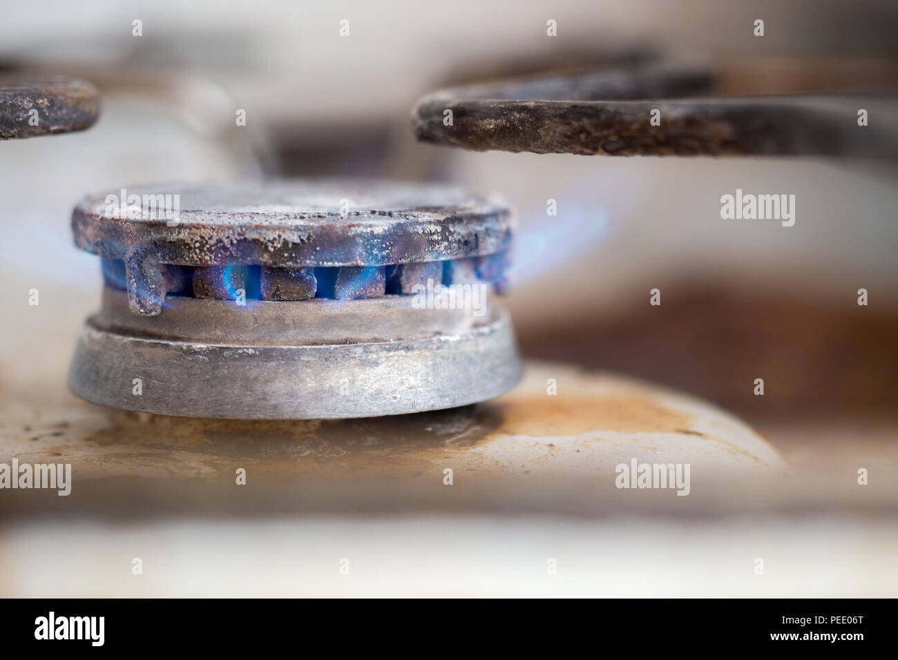 Close-up of dirty gas stove burning fire - Stock Image