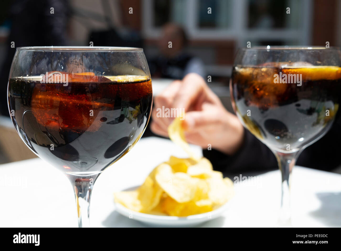 closeup of two glasses with vermouth, a fortified wine served on the rocks with a slice of orange, and a bowl with potato chips, eaten traditionally a - Stock Image
