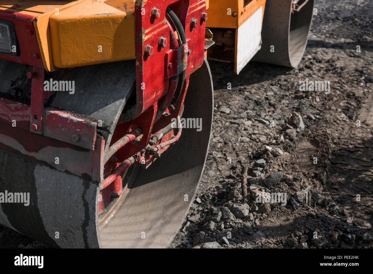 Orange Vibration roller compactor standing on a ground near asphalts road at road construction and repairing asphalt pavement works with a blue sky - Stock Image