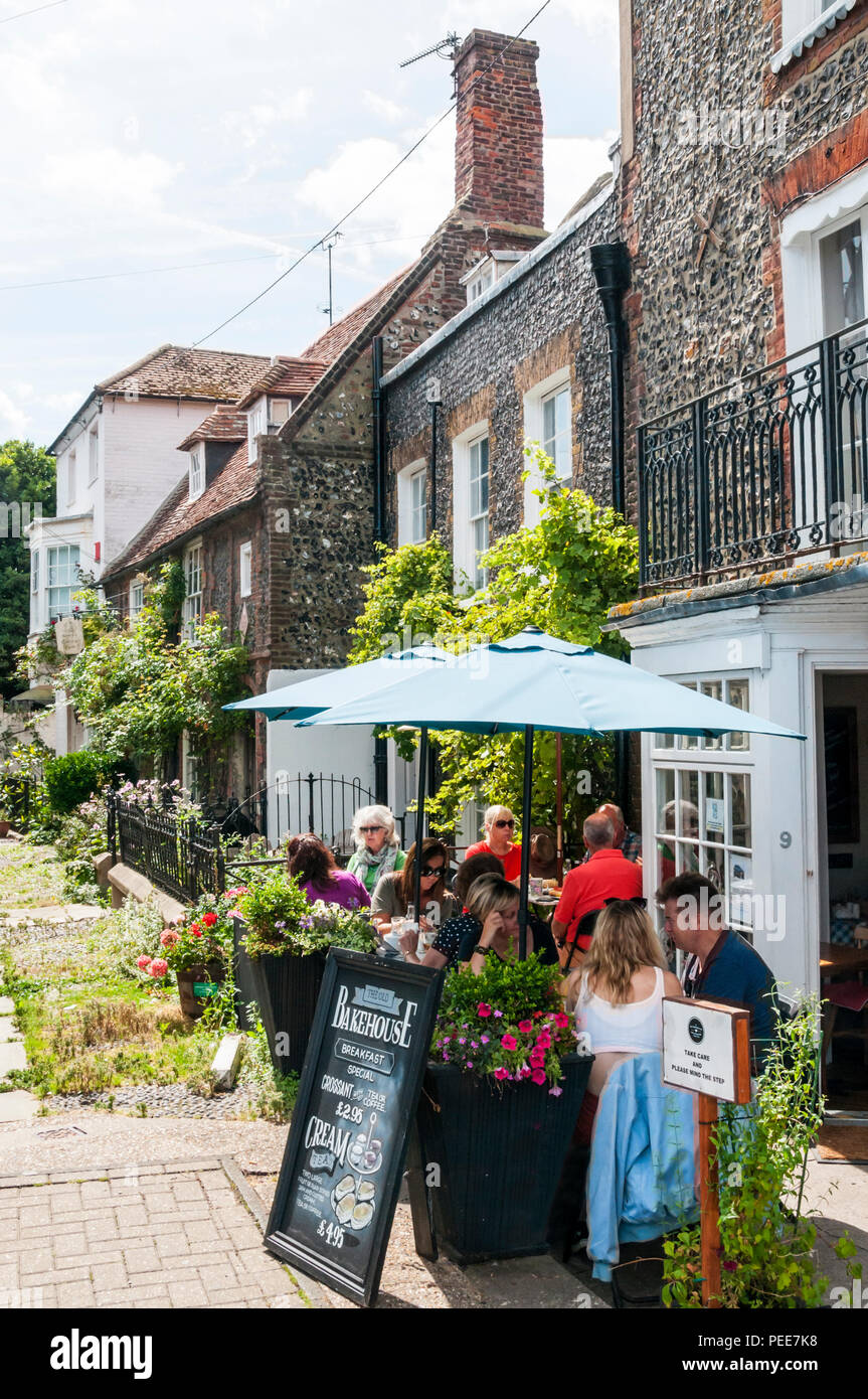 People sitting in the sunshine outside The Old Bakehouse cafe in Broadstairs. - Stock Image
