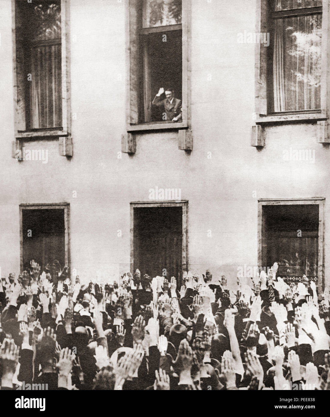 Germans cheering Hitler on hearing the news of his election as chancellor in 1933.  Adolf Hitler, 1889 – 1945.  German politician, demagogue, Pan-German revolutionary, leader of the Nazi Party, Chancellor of Germany (1933-1945) and Führer ('Leader') of Nazi Germany (1934 - 1945).  From These Tremendous Years, published 1938. - Stock Image