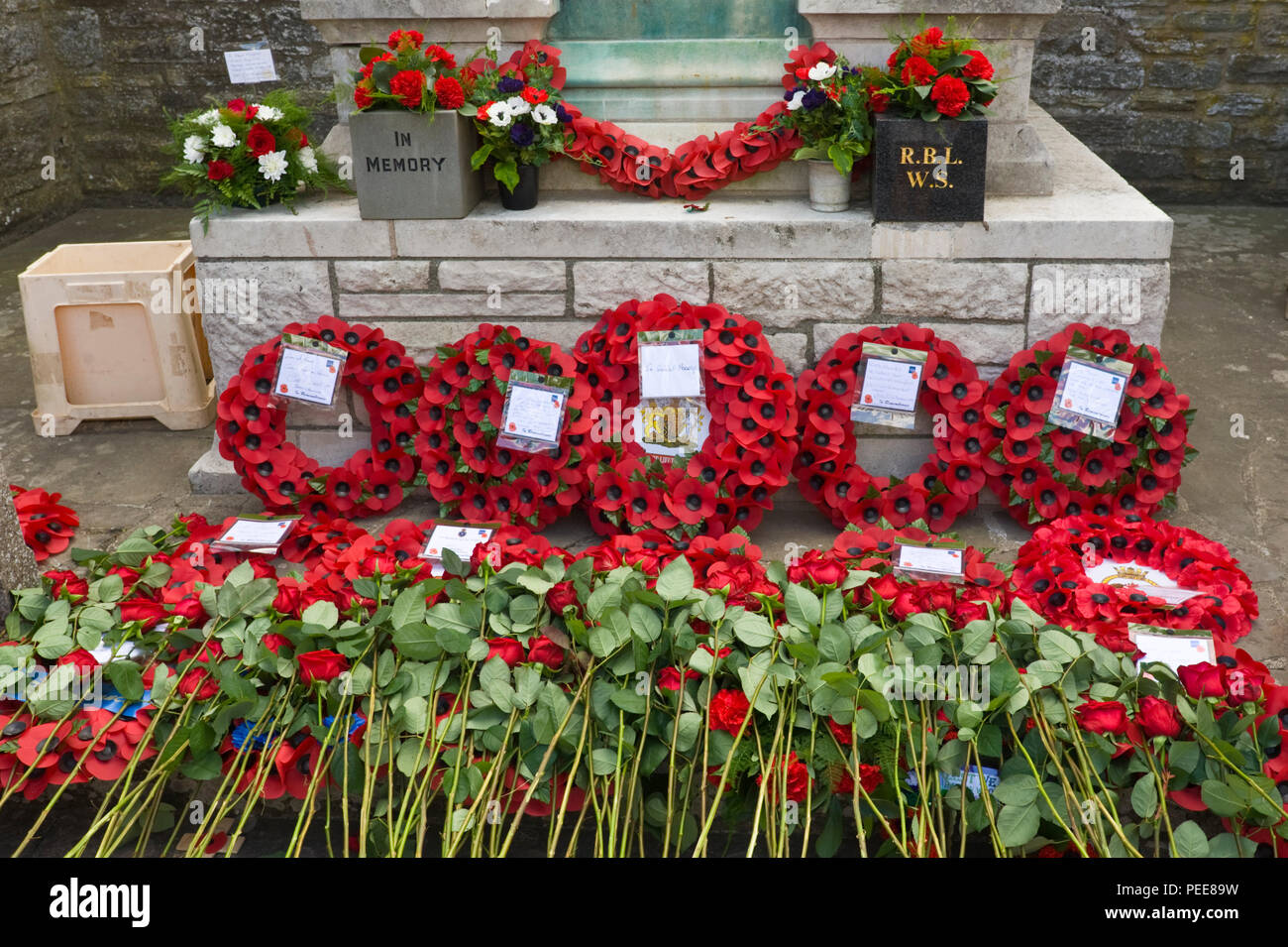 World War One commemorative event poppy wreaths & red roses laid around the War Memorial at Hay-on-Wye Powys Wales UK - Stock Image
