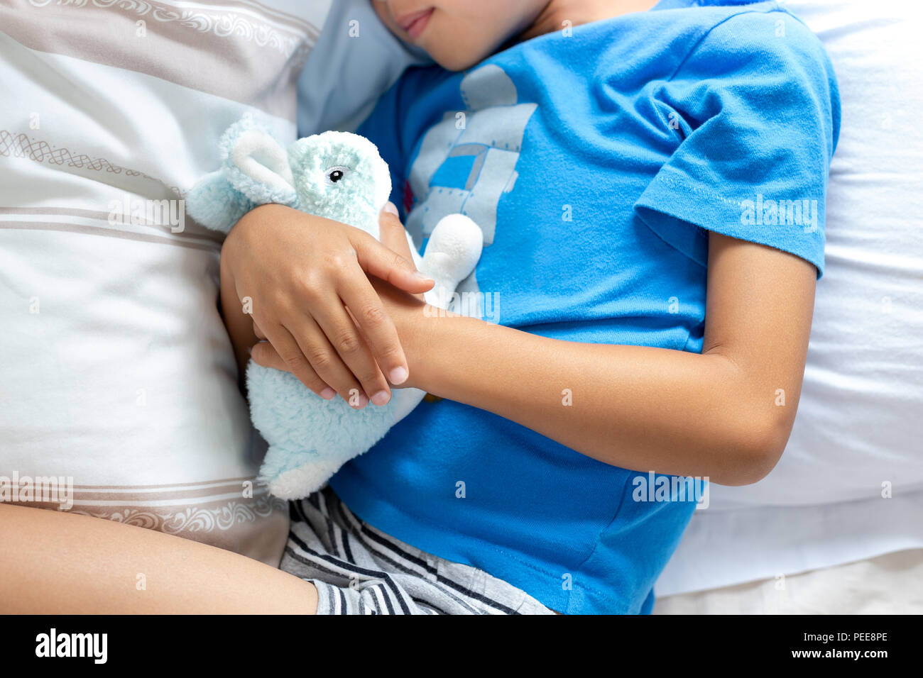 Little boy sleeping in bed holding his bunny robbit. - Stock Image