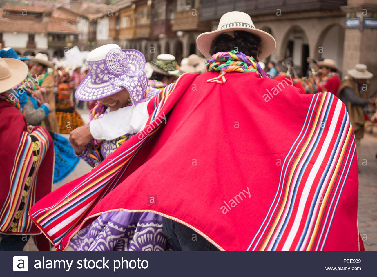 Men and women from the nearby regions of Cusco wear dresses and ponchos, singing and playing instruments at a yearly Carnival celebration of harvest and fertility in the Plaza de Armas in Cusco. Stock Photo