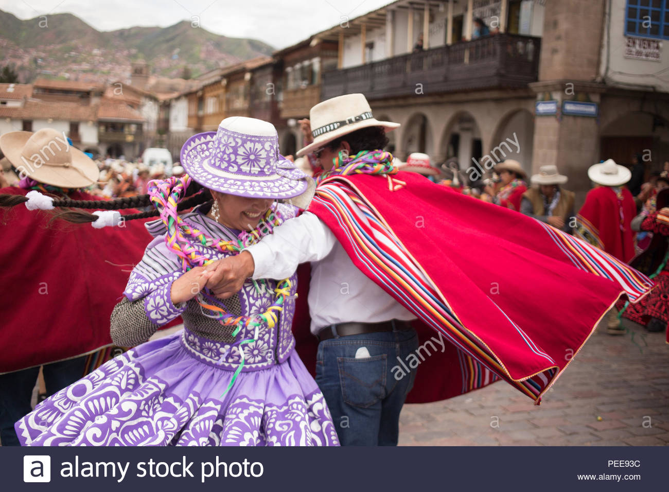 Men and women from the nearby regions of Cusco wear dresses and ponchos, singing and playing instruments at a yearly Carnival celebration of harvest and fertility in the Plaza de Armas in Cusco. - Stock Image