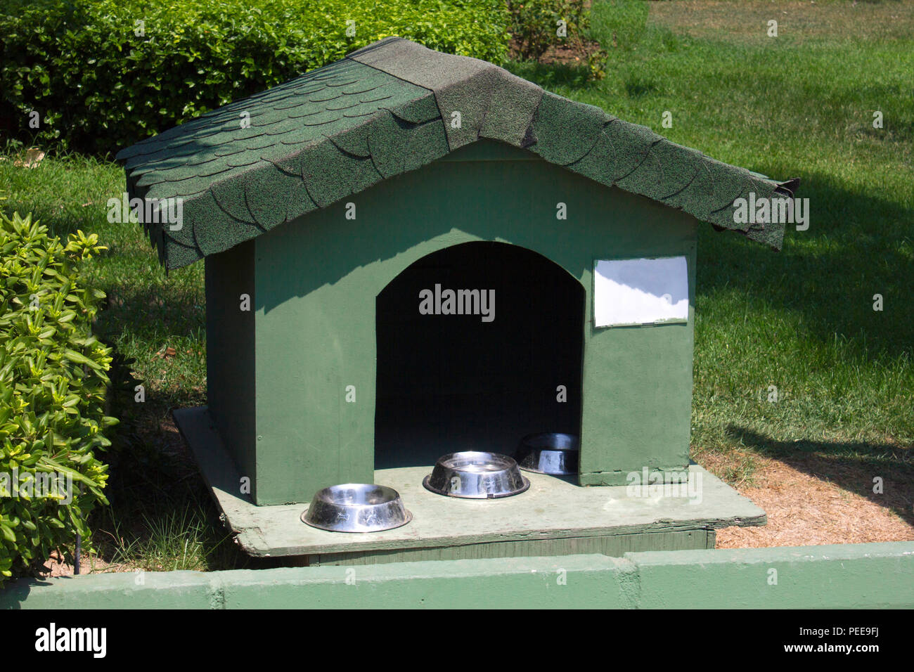 Cottage for cats with bowls for feed on a green lawn - Stock Image