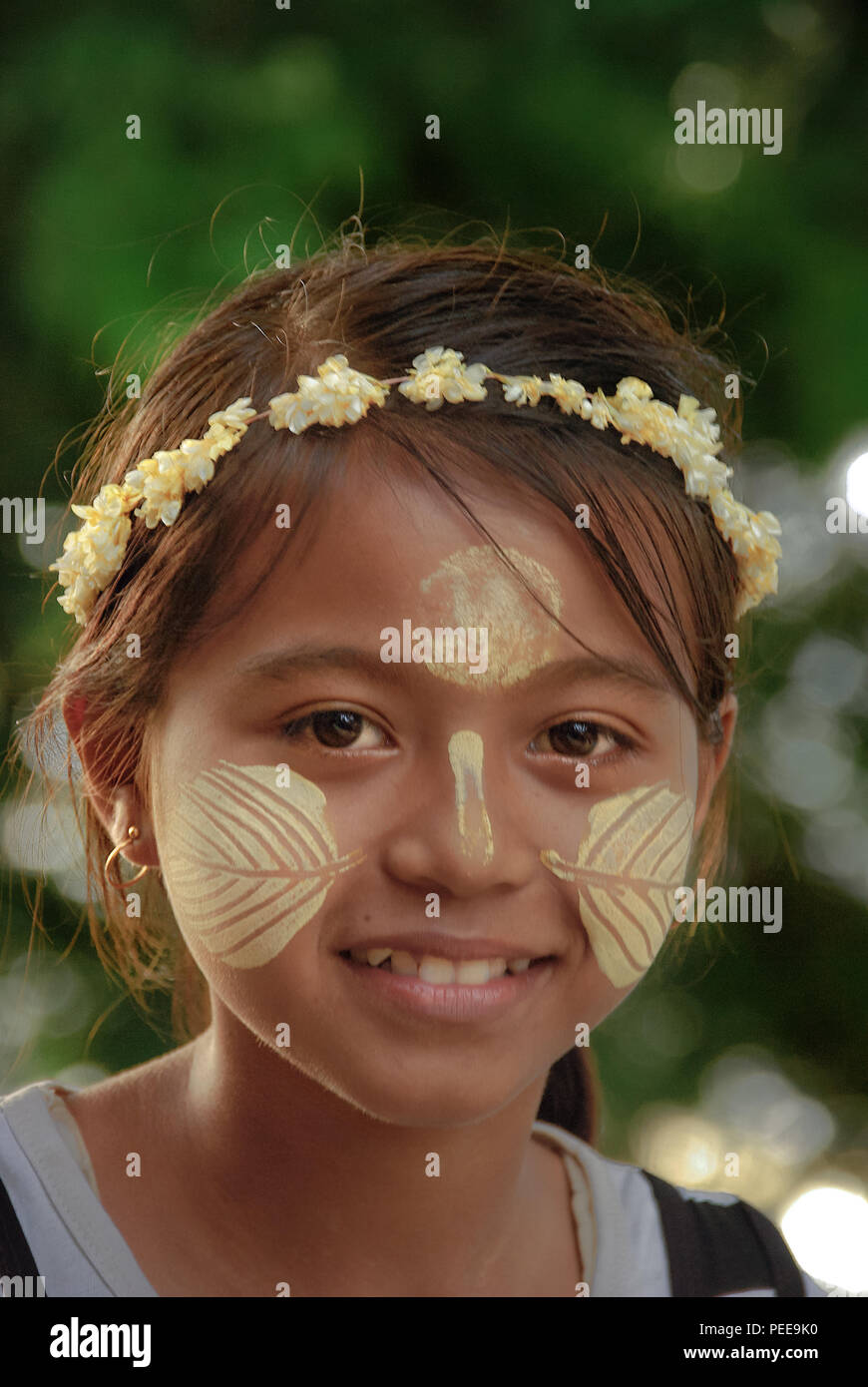 Burmese girl with a wreath on her head smiling looking straight at the camera. - Stock Image