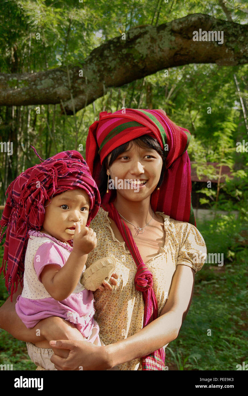 A young village woman is holding a child and smiling. - Stock Image