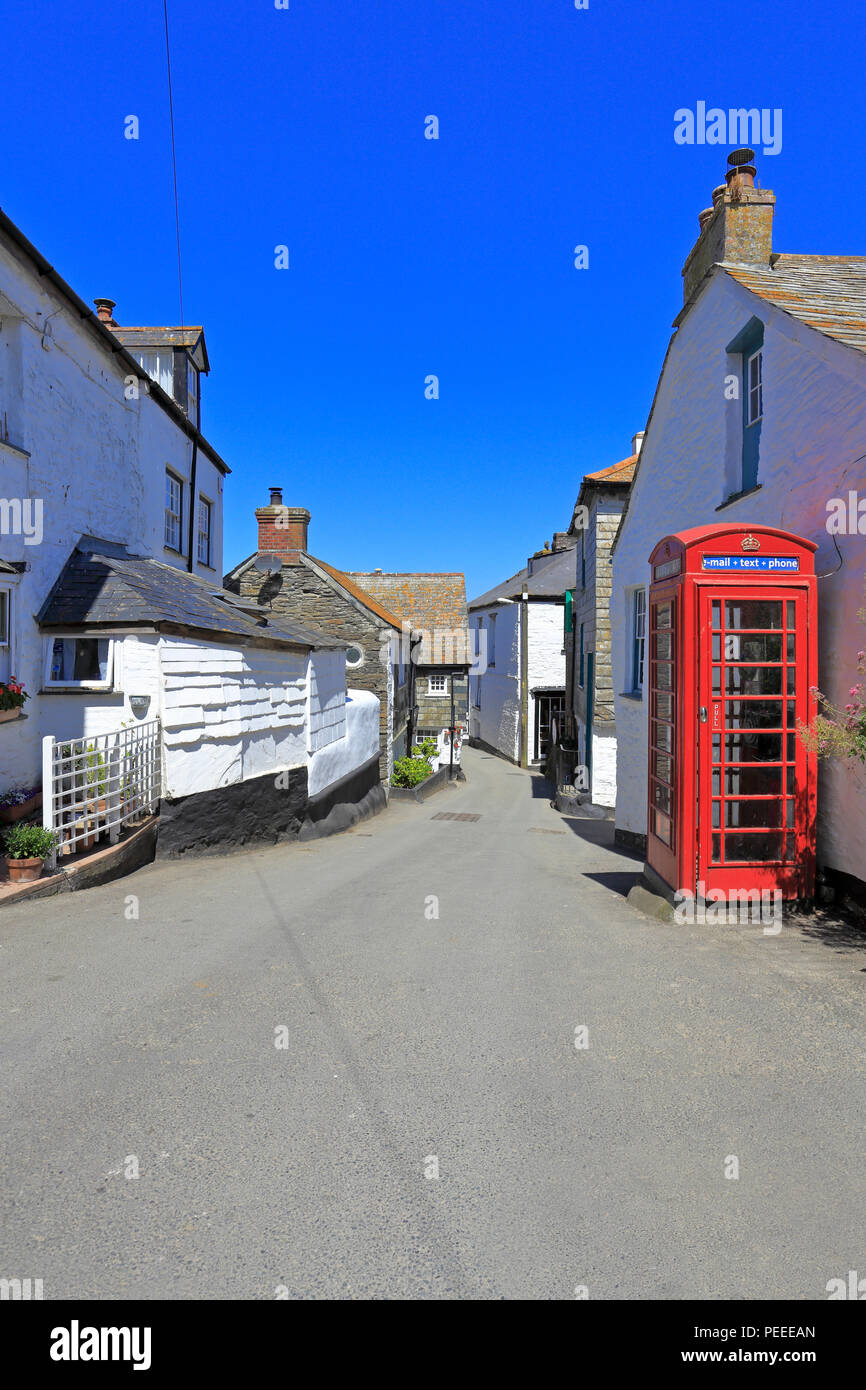 Whitewashed cottages and a red telephone kiosk on a narrow street in Port Issac, location of the ITV series Doc Martin, Cornwall, England, UK. - Stock Image
