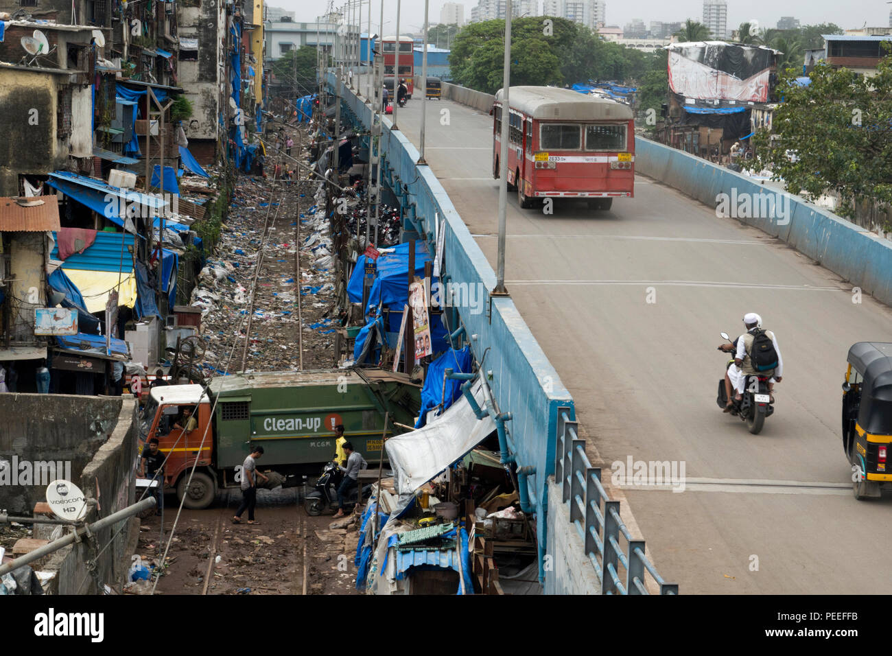 Rubbish truck passes under station road Station road and over train tracks covered in plastic trash at Bandra, Mumbai, India - Stock Image