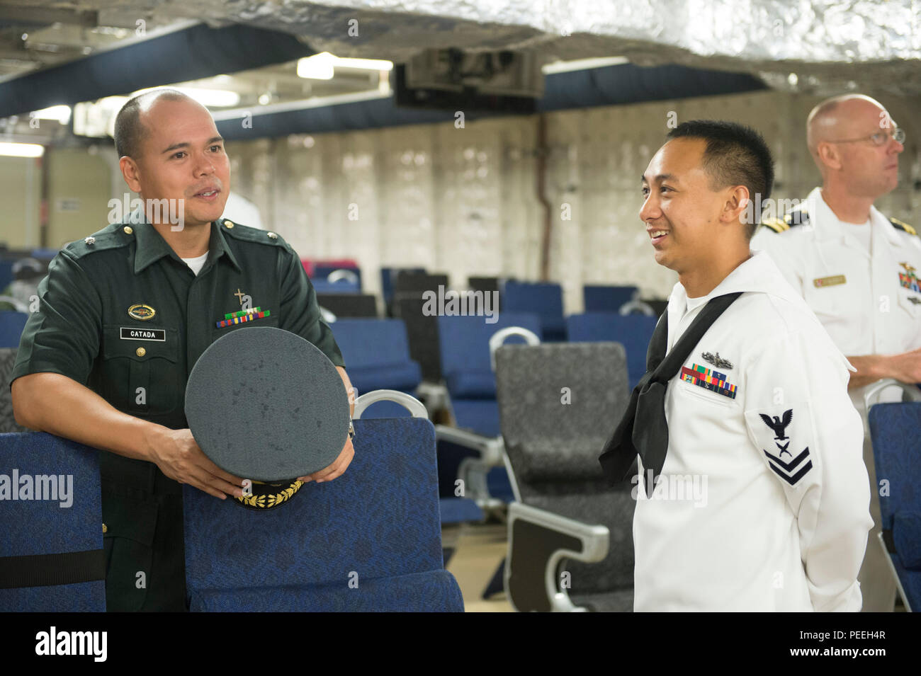 150814-N-MK341-009 SAN FERNANDO CITY, Philippines (August 14, 2015) – Yeoman 2nd Class Travis Aquino (right) speaks to Philippine Navy Chaplain Maj. Apolonio Catada during a closing reception aboard the Military Sealift Command joint high speed vessel USNS Millinocket (JHSV 3) Aug. 14. Millinocket and embarked Task Force Forager are serving as the secondary platform for Pacific Partnership, led by an expeditionary command element from the Navy's 30th Naval Construction Regiment (30 NCR) from Port Hueneme, Calif. Now in its 10th iteration, Pacific Partnership is the largest annual multilateral  - Stock Image