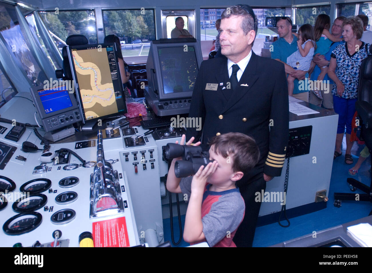 Motor Vessel Mississippi Captain Lee Hendrix watches as Garrett Durrett, 5, of Pelham, Ala., looks through a pair of binoculars during a public tour of the vessel docked at Ross's Landing in Chattanooga, Tenn., Aug. 7, 2015. The M/V Mississippi spends more than 90 percent of its time as a working towboat, moving barges, equipment and supplies on the lower Mississippi River. The M/V Mississippi, built in 1993 by Halter Marine, is the fifth Army Corps of Engineers towboat to bear the name.  It is the largest diesel towboat in the United States at 241-feet long, 58-feet wide and five stories high - Stock Image