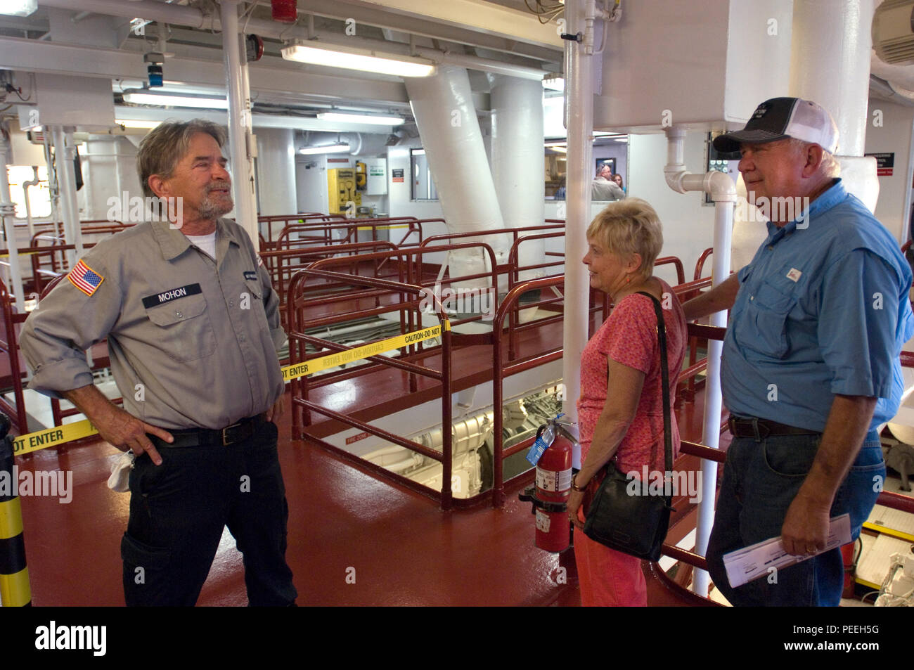 Walker Mohon (Left) welcomes visitors to the engine room of the Motor Vessel Mississippi during a public tour of the vessel docked at Ross's Landing in Chattanooga, Tenn., Aug. 7, 2015. The M/V Mississippi spends more than 90 percent of its time as a working towboat, moving barges, equipment and supplies on the lower Mississippi River. The M/V Mississippi, built in 1993 by Halter Marine, is the fifth Army Corps of Engineers towboat to bear the name. It is the largest diesel towboat in the United States at 241-feet long, 58-feet wide and five stories high. Three 2,100-horsepower diesel engines  - Stock Image
