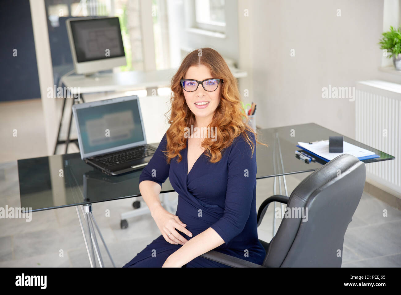 Portrait of pregnant woman sitting at office desk while looking at camera and smiling. Part time job. - Stock Image