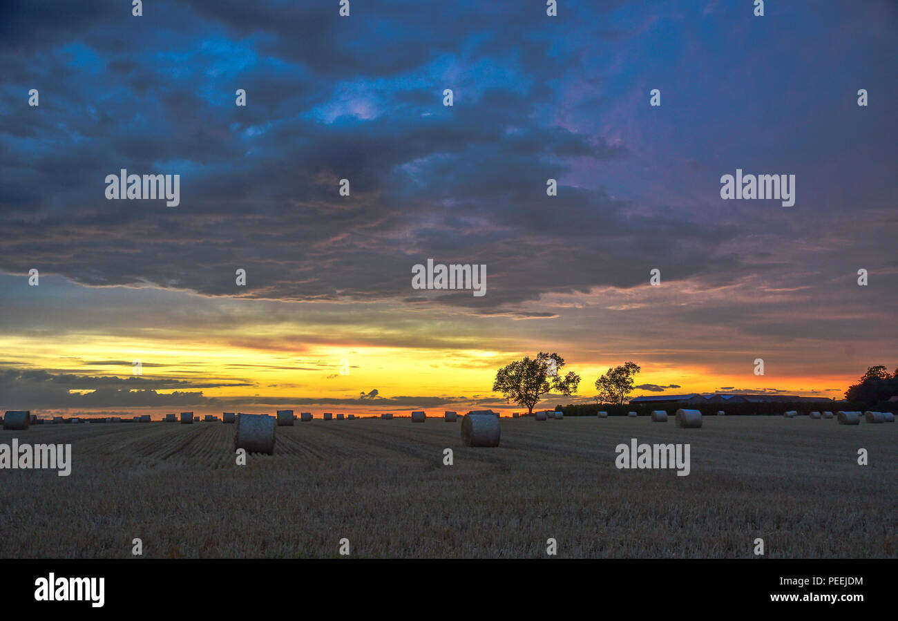 A sunset sunrise over a field of corn stubble with hay bails dotted around - Stock Image