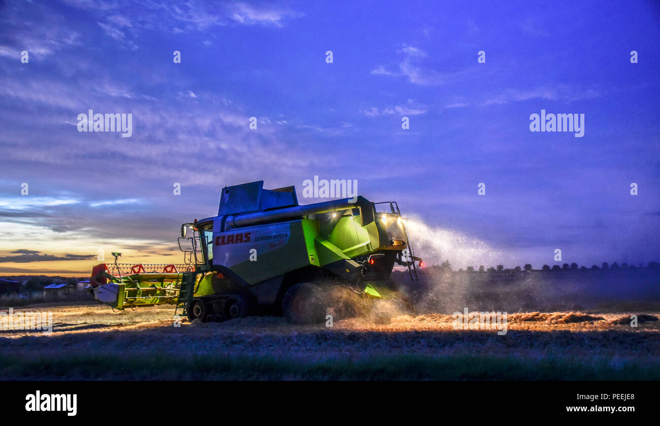 Combine harvester at dusk harvesting a field of corn dust pouring out of the back Stock Photo