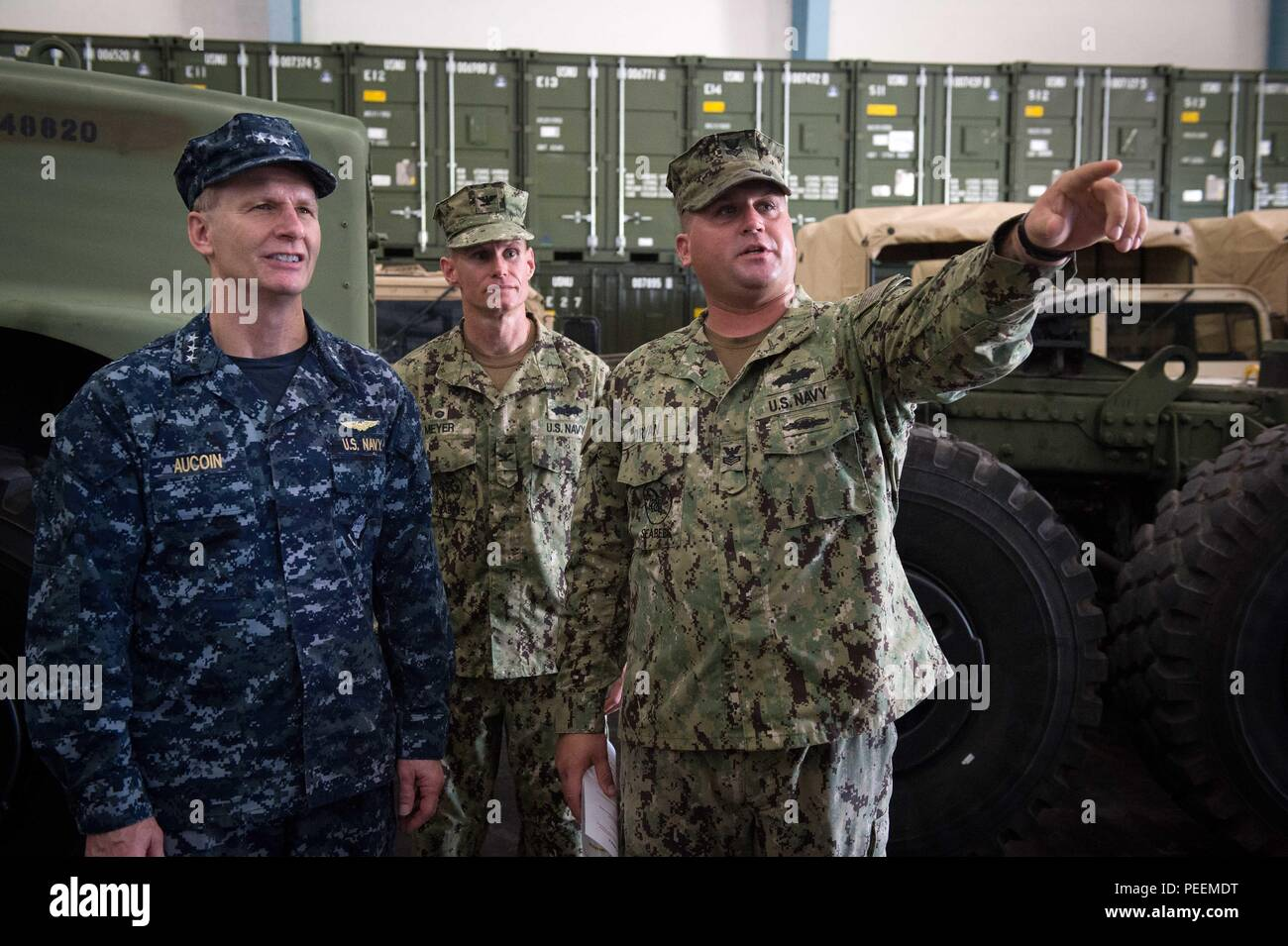 Construction Mechanic 1st Class Garrett Oryan (Right), assigned to Naval Mobile Construction Battalion (NMCB) 1, briefs Vice Adm. Joseph P. Aucoin, Commander, U.S. Seventh Fleet, and Capt. James G. Meyer, Commodore, 30th Naval Construction Regiment (NCR), on NMCB 1 civil engineer support equipment (CESE) capabilities at Naval Base Guam, Jan. 22, 2016. NMCB 1 provides expeditionary construction and engineering (combat service support) to include horizontal and vertical construction; maintenance and operation of expeditionary bases and facilities; tactical sustainment bridging, Humanitarian Assi - Stock Image