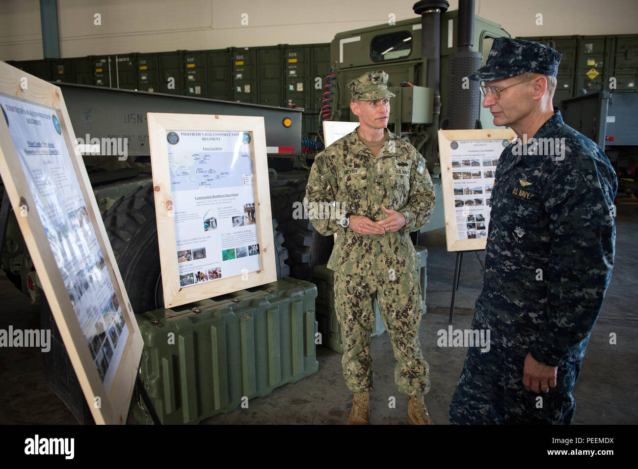 Capt. James G. Meyer, Commodore, 30th Naval Construction Regiment (NCR), briefs Vice Adm. Joseph P. Aucoin, Commander, U.S. Seventh Fleet, on NMCB 1 civil engineer support equipment (CESE) capabilities at Naval Base Guam, Jan. 22, 2016. NMCB 1 provides expeditionary construction and engineering (combat service support) to include horizontal and vertical construction; maintenance and operation of expeditionary bases and facilities; tactical sustainment bridging, Humanitarian Assistance (HA) through Construction Civic Action Details (CCAD) and Civic Action Teams (CAT) and theater disaster respon Stock Photo
